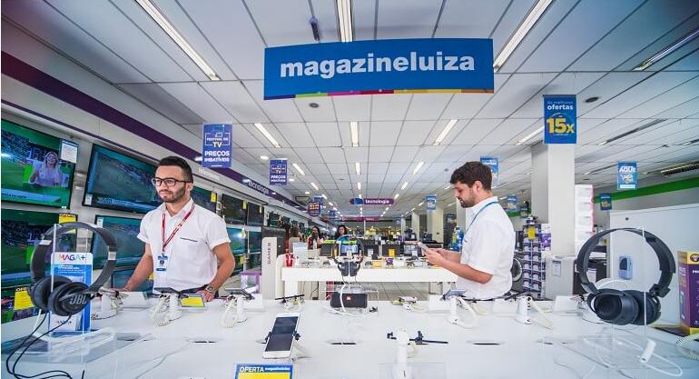 Imagem de uma loja física do Magazine Luiza que mostra dois vendedores, Um deles está com o celular nas mãos.